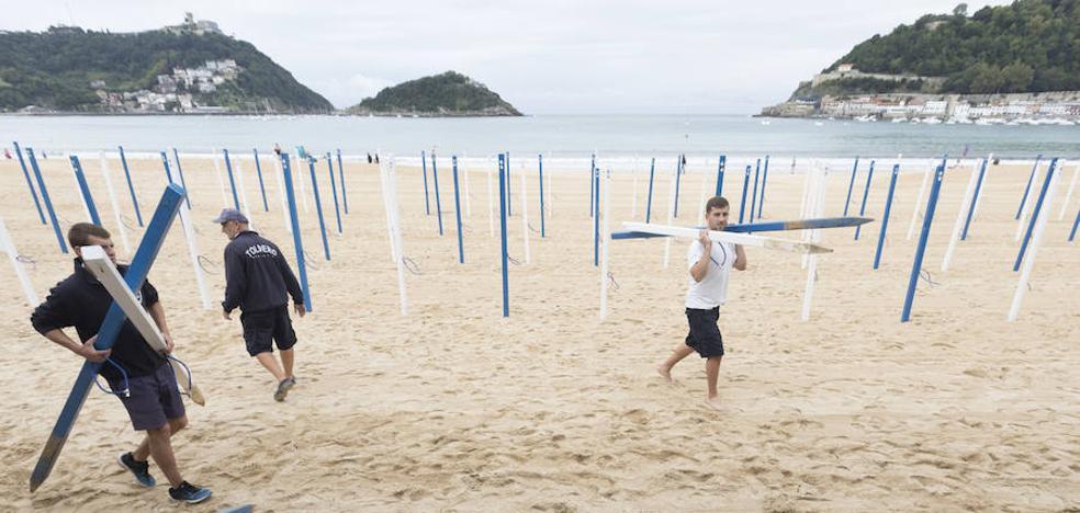 La retirada de los toldos en las playas donostiarras, preludio del fin del verano