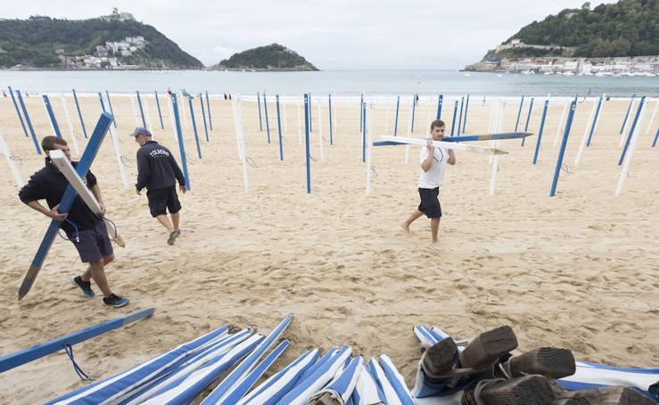 La retirada de los toldos en las playas, preludio del fin del verano donostiarra