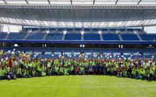 Los trabajadores posan antes del reestreno de Anoeta junto a los jugadores de la Real Sociedad