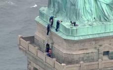 Una manifestante se encarama a la Estatua de la Libertad para confrontar las política de Trump