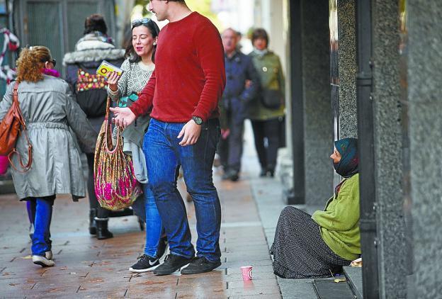Una mujer sentada junto a la puerta de una entidad bancaria en el paseo de Colón. /  F. DE LA HERA