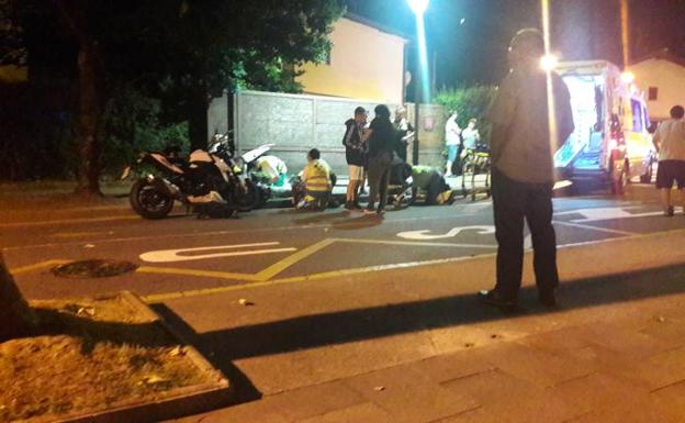 Sanitarios atienden a las dos personas que viajaban en la moto que fue golpeada por el coche que se dio a la fuga. /