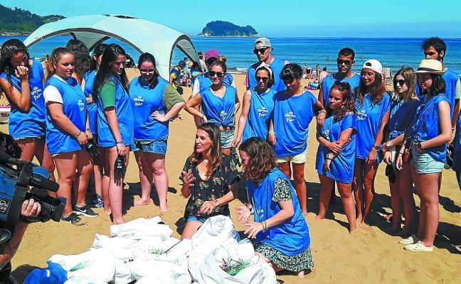 Decenas de voluntarios limpian el arenal de la playa de Zarautz