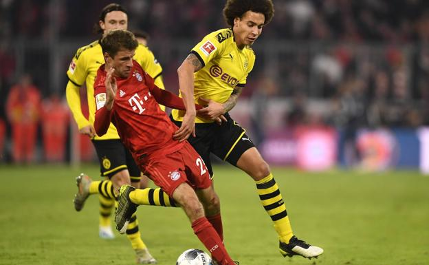 Müller and Witsel dispute a ball during a duel between Bayern Munich and Borussia Dortmund.