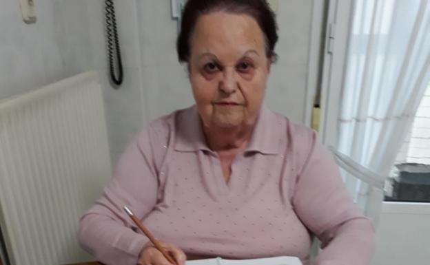 Maribel Puente, usuaria del Centro de Mayores de Behobia, haciendo los ejercicios que le envían las dinamizadoras, en la cocina de su casa./