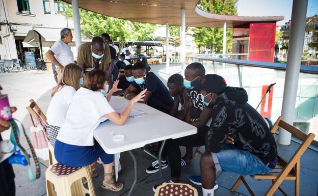 Voluntarias de Irungo Harrera Sarea atienden a varios de los 149 migrantes llegados la semana pasada. / DE LA HERA