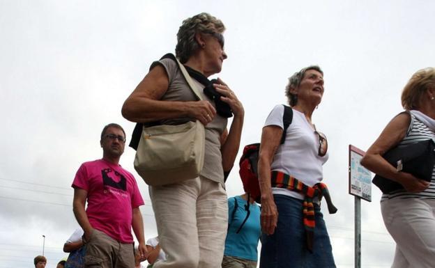 Un grupo de personas camina siguiendo las señales jacobeas en Irun. /