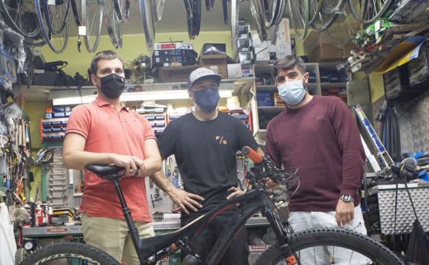 Ander Iturri y Borja Olazabal flanquean a Gorka Gabellanes, uno de los responsables de la tienda y taller de bicicletas Cyclope. / F. DE LA HERA